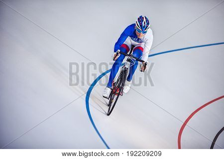 Cyclist pedaling on a racing bike on velodrome outdoors