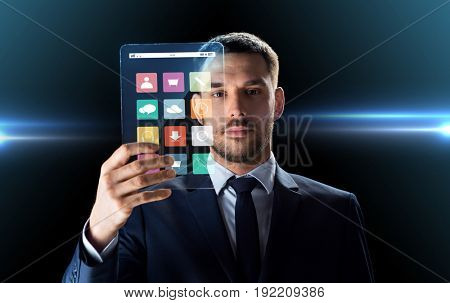 business, multimedia and future technology concept - businessman in suit working with media icons on transparent tablet pc computer screen over black background