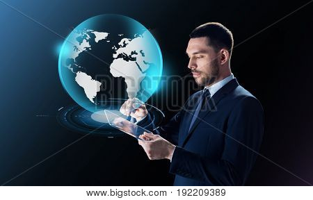 business, people and modern technology concept - businessman in suit working with transparent tablet pc computer and virtual earth projection over black background