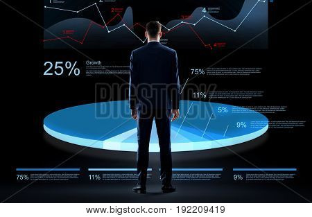 business, people and statistics concept - businessman in suit with virtual pie chart hologram over black background