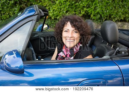 Happy Brunette Curly In Blue Car In Summer