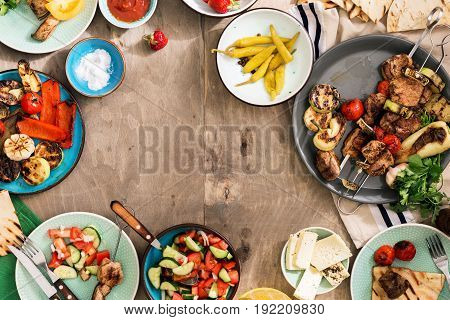 Frame made of different food cooking on the grill. Shish kebab grilled vegetables salad and snacks. Dinner table concept
