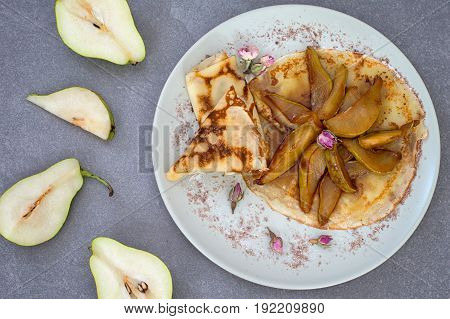 Pancakes with caramel pears. Horizontal, rustic style. Gray stone background. Top view. Close-up