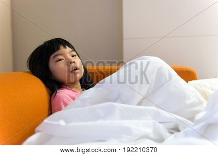 Sick little child lying on sofa and cover with blanket