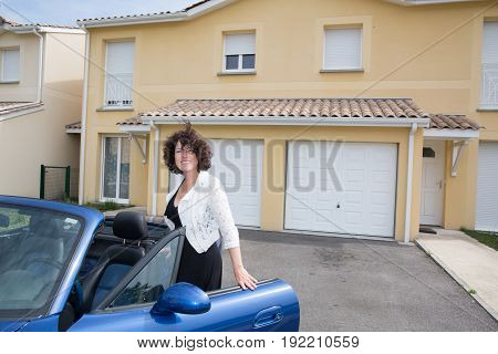 Woman Open Door Of Convertible Car Near House Home In Summer Day