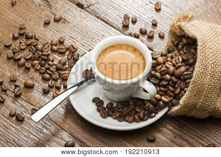 cup of coffee with burlap sack and coffee beans on wooden table.