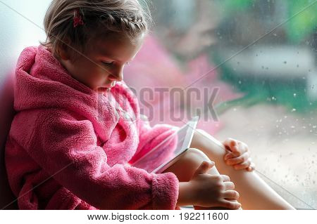 Cute little girl in pink bathrobe using tablet pc. Sitting on the window sill.