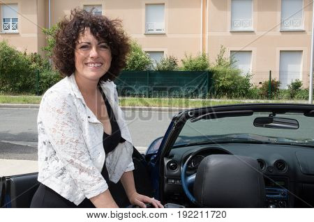 a forties woman in street with car