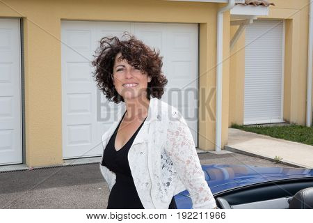 Smiling Forties Brunette Woman With Car And Home House In Back