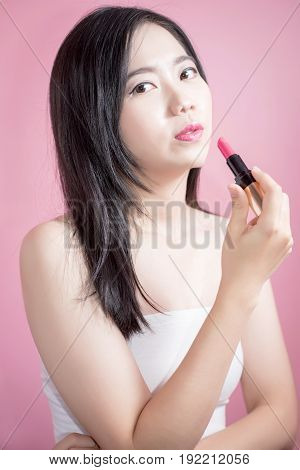 Long hair asian young beautiful woman lipstick isolated over pink background. natural makeup skincare cosmetology and plastic surgery concept