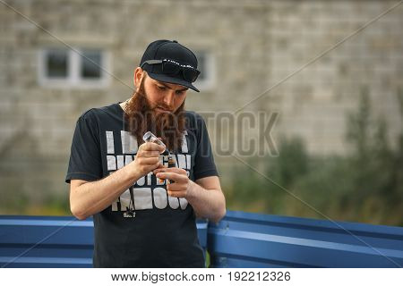 Vape Bearded Man In Real Life. Portrait Of Young Guy With Large Beard In A Cap And Sunglasses Vaping