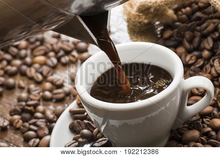 pouring coffee from coffeepot into white coffee cup closeup.