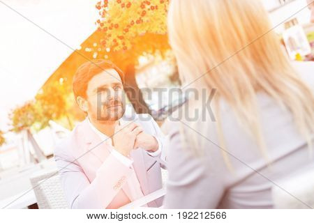 Businessman sitting with female colleague at sidewalk cafe