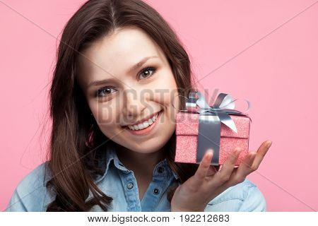 Portrait of charming girl in casual shirt holding small giftbox and looking at camera on pink background.