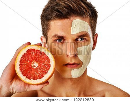 Facial mask from fresh fruits and clay for man concept. Face with treatment mud applied . Male holding grapefruit half for skin care procedure salon. Grapefruit are main ingredient in cosmetic masks.