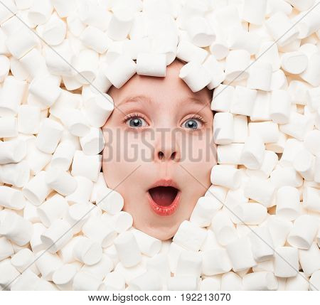 From above shot of expressive boy lying in white fluffy marshmallows and looking surprisingly at camera.