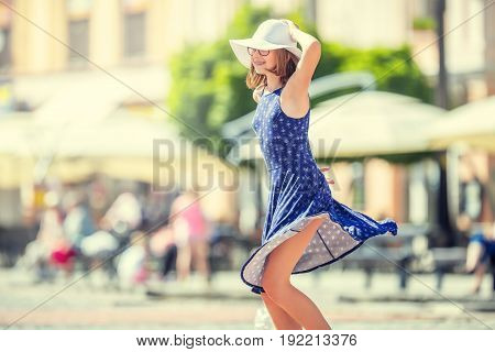 Beautiful cute young girl dancing on the street from happiness.Cute happy girl in summer clothes dancing in the sun.