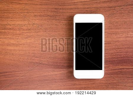 Empty Screen Of Mobile Phone Above Brown Table Top View, Leave Space For Display Of Your Content, Te