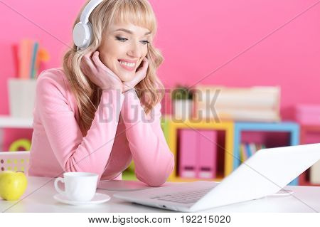 Beautiful young woman in headphones using laptop in room with pink walls