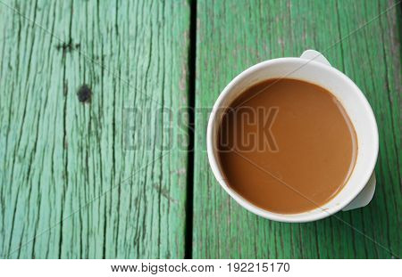 start your day with a cup of coffee,instant coffee paper cup on green wood table