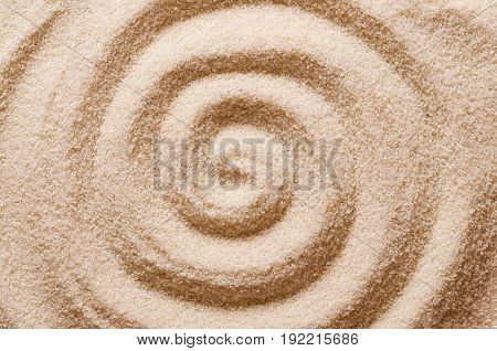 Spiral in the sand. Archimedean spiral made with the finger in dry ocherous sand. Macro photo close up from above.