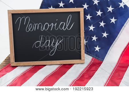 American flag and slate with text memorial day on wooden table