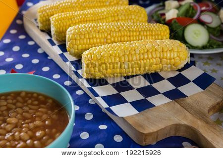 Close-up of baked beans and corn cob on wooden table with 4th july theme