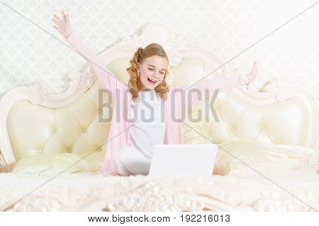 Happy little girl sitting on couch and using modern laptop
