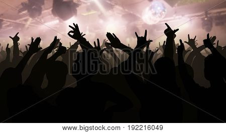 Silhouettes Of Concert Crowd With Hands Raised At A Music Disco