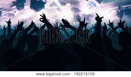 Silhouettes Of Dancing People In Front Of Bright Stage Lights