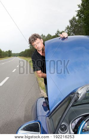 Handsome Man With Trouble With Blue Car On Road