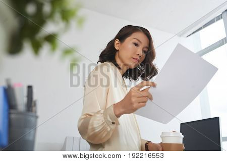 Low angle portrait of young Asian businesswoman reading document at office