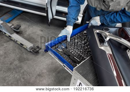 The mechanic selects the tool. tools for service station. A large set of tools for any size of nuts. In a special drawer. spanners and socket nozzles. can use to display or montage product or make a website for service