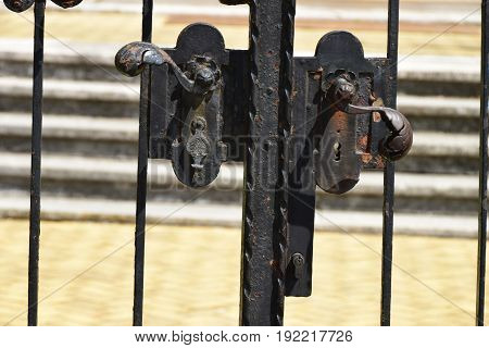 Old wrought iron lock on the metal gate, , with stairs in background