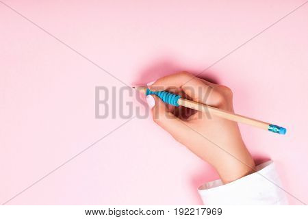 Hand with stylish pencil on pastel pink background. Copy space, flat lay style.