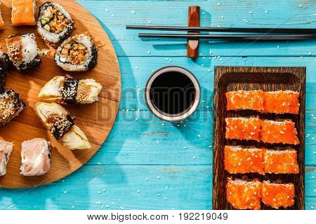 Photo of two sets of sushi on blue table