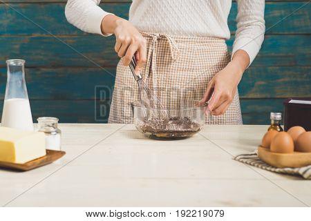 House wife wearing apron making. Steps of making cooking chocolate cake. Preparing dough mixing ingredients