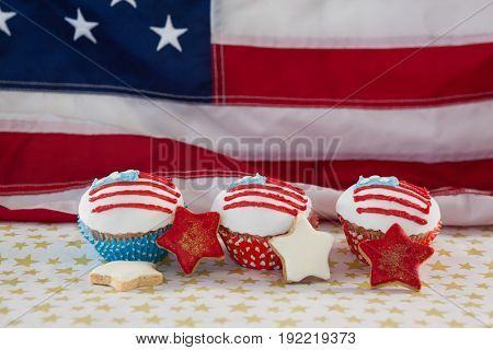 Close-up of decorated cupcakes and cookies arranged on table against American flag