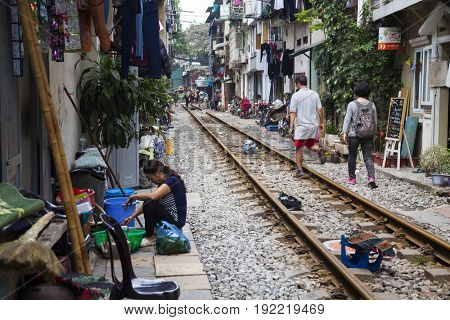 Hanoi, Vietnam - March 18, 2017:  Locals live their life on and around the train line passing between buildings in the Old Quarter of Hanoi.