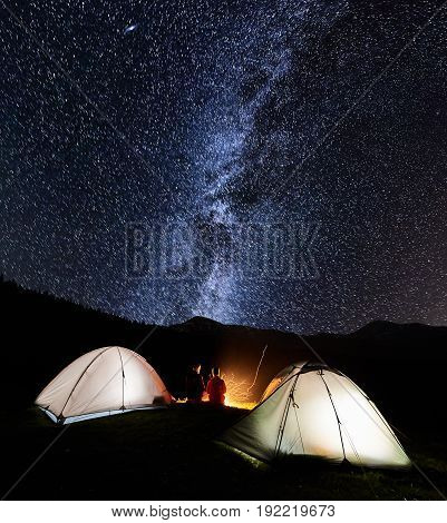 Night Camping In The Mountains. Rear View Of Romantic Couple Tourists Have A Rest At A Campfire Near