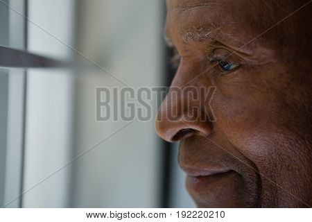 Close up of thoughtful senior man looking out through window at home