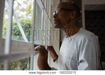 Senior man wearing eyeglasses while looking out through window at home