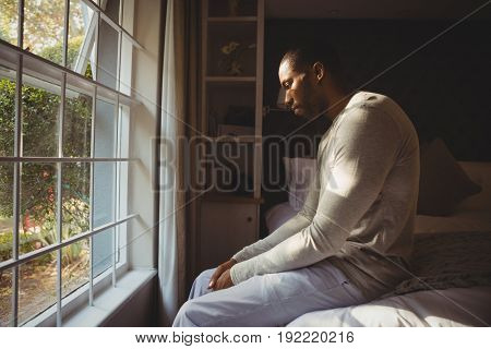 Side view of sad man sitting on bed by window at home