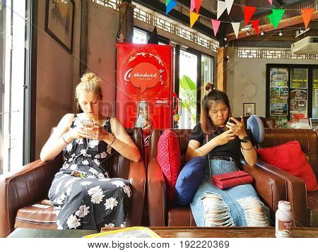 CHIANG RAI THAILAND - JUNE 1 : unidentified two caucasian using mobile phone on vintage sofa in a hostel on June 1 2017 in Chiang rai Thailand.