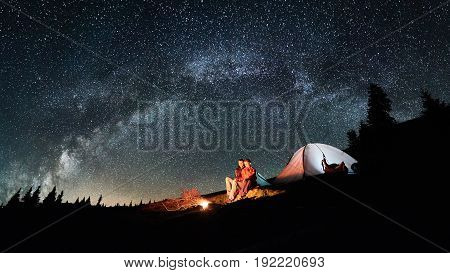 Night Camping. Romantic Couple Tourists Have A Rest At A Campfire Near Illuminated Tent Under Amazin