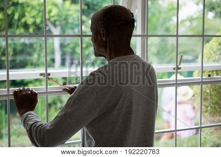 Rear view of senior man looking out through window while standing at home