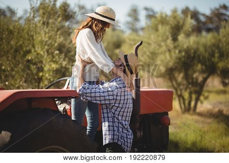 Young couple looking at each other while standing by tractor at olive farm