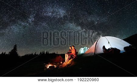 Night Camping In The Mountains. Man And Woman Tourists Sitting At A Campfire Near Two Illuminated Te