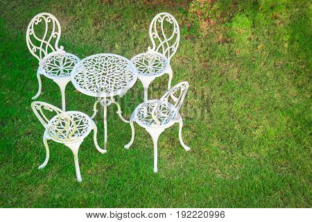 Outdoor white table and chairs in a garden on green lawn