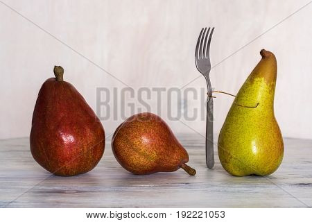 Three pears on a wooden table . Conceptual photos. One pear with a fork. Composition with pears.